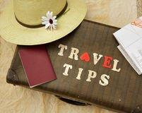 travel-tips-summer-hat-flower-old-suitcase-brown-passport-map-wooden-letters-58673215